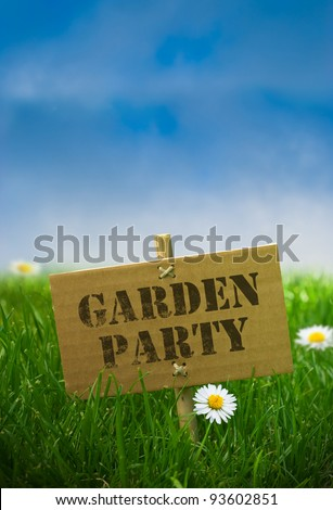 garden party text written onto a carton panel fixed by using bamboo post, nature background with daisy flowers green grass and blue sky