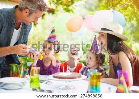 garden party with family for little girl's birthday, Dad tries to light the candles on the cake , the garden is decorated with balloons and colors are bright #274898858