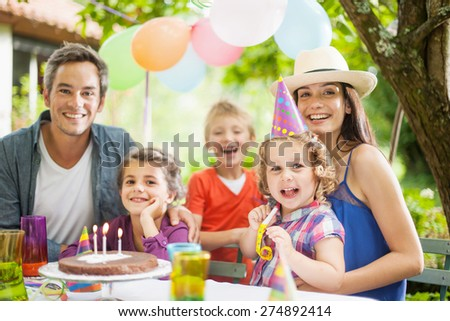 garden party with family for little girl's birthday, the whole family looking at camera, the garden is decorated with balloons and colors are bright #274892414