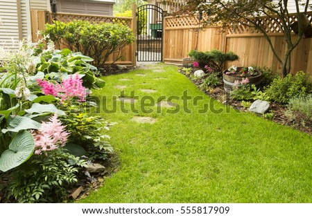 Garden Path. Back yard path leads past garden in bloom during transition from spring to summer. #555817909