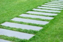 Garden path. Slate stepping stones embedded in lawn. Green, natural grass, gray, rectangular tiles. Abstract composition. Image