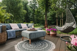 Garden patio decorated with Scandinavian wicker sofa and coffee table