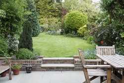 Garden patio with furniture and lawn in a typical English back garden in London, UK