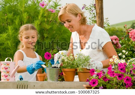 Garden, planting concept - mother with daughter planting flowers into the flowerpot