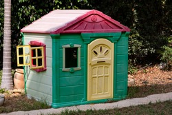 Garden playground for children with lovely little house. Summer kids house in green garden, playhouse cottage for children's play. Green playhouse in a garden.