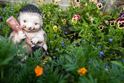 garden sculpture hedgehog with a guitar in flowers, horizontally