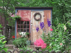 Garden shed she-shed with rustic construction surrounded by blooming perennial flowers