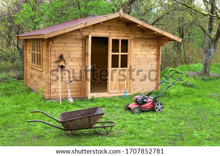 Garden shed with hoe, string trimmer, grass-cutter and old barrow outside. Gardening tools shed. Garden house on lawn in garden. Wooden tool-shed. Hovel made of timber in domestic environment.