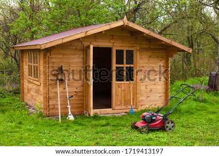 Photo of  Garden shed with hoe, string trimmer,  rake and grass-cutter. Gardening tools shed. Garden house on lawn in garden. Wooden tool-shed. Hovel made of timber in domestic environment.