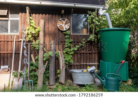 garden shed with rain water recycling system and old fashioned gardening tools