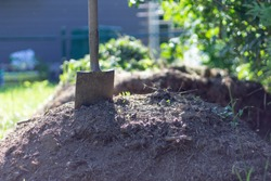Garden shovel on compost. Freshly composted earth from compost bin. nutrient rich vegetables converted to soil.