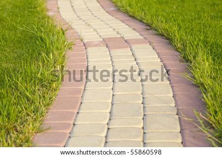 Garden stone path with grass growing up between and around stones, Brick Sidewalk