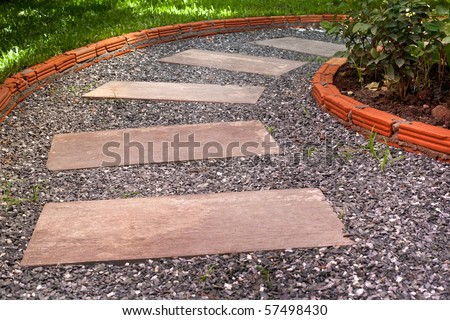 garden stone path with pebble stone , brick and grass.