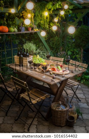Garden table with appetizers and wine in the evening - Shutterstock ID 1016554402