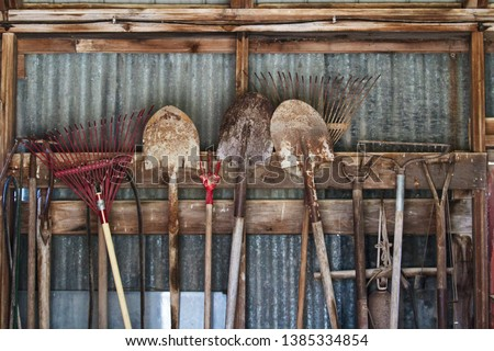 Garden tools hanging in a row in a shed; shovels and rakes hooked on a wooden beam in a line #1385334854