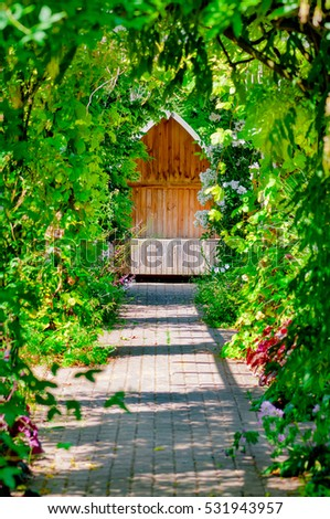 Garden trellis walkway hideout hidden tranquil sitting bench area outdoors empty shaded by vine and roses #531943957