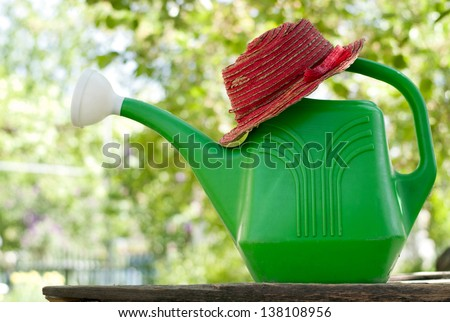 Garden watering can in the garden green and red hat