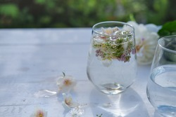 garden wedding drinks. transparent non alcoholic drink with flower decoration. outdoors wedding. white flowers in a tonic water. wooden table with glasses on it.