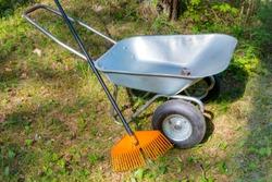 garden wheelbarrow with a rake on lawn