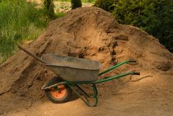 Garden-wheelbarrow with near a pile of sand on a farm. Selective focus