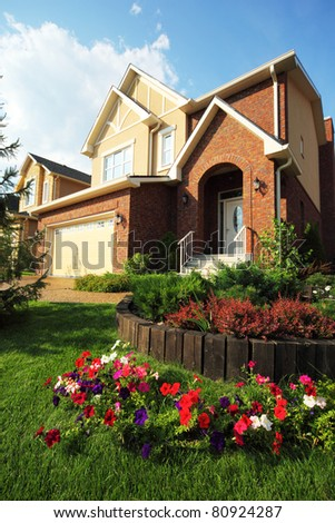 Garden with beautiful flowers in front of new two-storied brick cottage