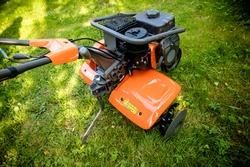 garden with tiller machine. Garden tiller to work, close up.Abstract and conceptual of motor hoe at work. garden with rototiller , tiller tractor, cutivator, miiling machine. Man plowing the garden