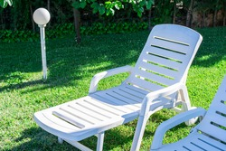 Garden with white plastic sun loungers on freshly cut grass