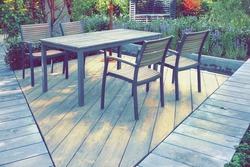Garden Wooden Patio with Wooden Dinning Table and Chairs on Harwood Decking Floor. Private Family Place On Backyard Garden. Wooden Terrace In Garden With Outdoor Furniture. Landscaped Backyard.