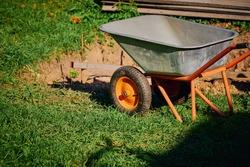 Garden work and tools. A metal garden wheelbarrow stands on a green lawn next to a dug place