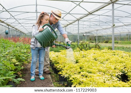 Gardener and granddaughter watering plants in greenhouse