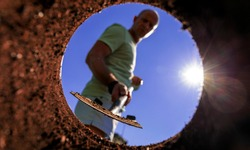 Gardener digging with garden spade in black earth soil. Farming, gardening, agriculture and people concept. Under view man with shovel digging.