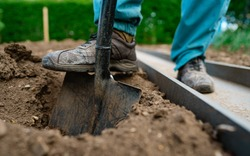 Gardener digging with garden spade in earth soil.farming, Soil preparing for planting in spring. Digging the earth to plant potatoes. Agriculture and people concept