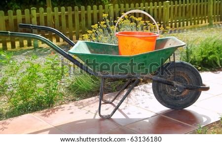 gardener green wheel barrow with orange pail cube tools