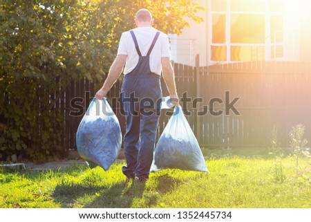 Gardener in uniform carries compost in bags after cleaning the ground.the employee in the sunlight. #1352445734