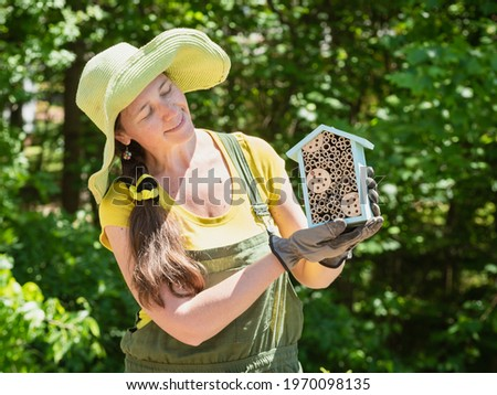 Gardener is holding a house for bees or other pollinators. Stock photo ©