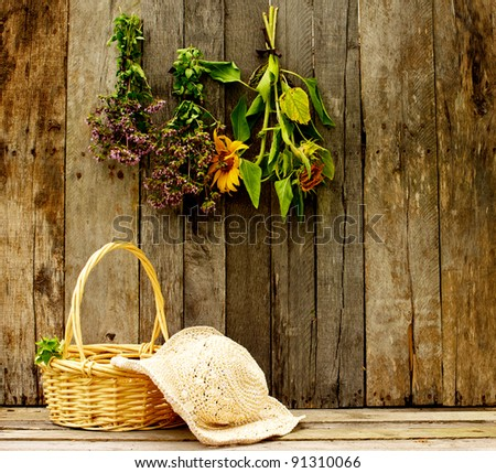 Gardener's straw hat and basket of freshly cut oregano and herbs hanging on an aged barn board background.