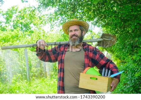 Gardener work. Farm. Happy bearded man in garden. Plants. Garden tools. Gardening. Eco-farm. Work in garden. Bearded man with gardening tools. Work in garden.