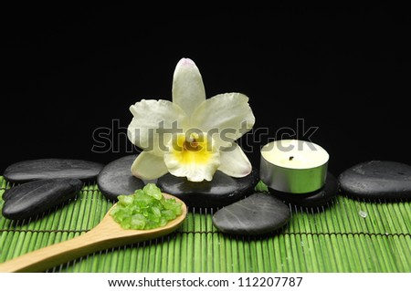 Gardenia and stones with soap, towel and candle on green mat