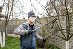 Gardening. A man in a white mask, glasses and black gloves cuts branches on trees in his backyard garden. COVID-19. Coronavirus in Europe. Pandemic life.