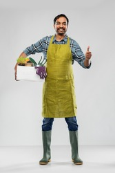 gardening, farming and people concept - happy smiling indian male gardener or farmer in apron and rubber boots with box of garden tools showing thumbs up over grey background
