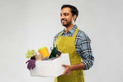 gardening, farming and people concept - happy smiling indian male gardener or farmer in apron with box of garden tools over grey background