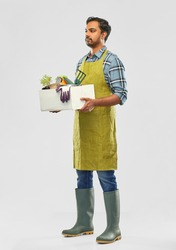 gardening, farming and people concept - indian male gardener or farmer in apron and rubber boots with box of garden tools over grey background