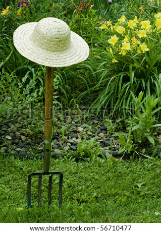 gardening fork and straw hat with a background of flowers