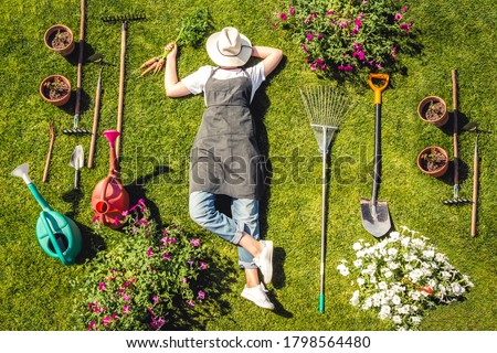 Gardening  Gardener Girl Relaxed Lying  Green Grass, Surrounded Gardening Tools With Plants Workplace home among plants  home garden ,agriculture, freelance, work  home, slow life, mood