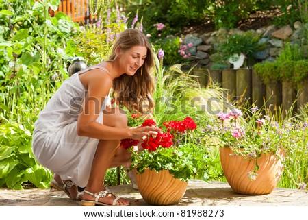 Gardening in summer - happy woman with flowers her garden - stock photo