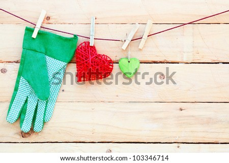 Gardening Love. The beautyful feeling of yard work. Some hearts and gardening hand gloves on a wooden background