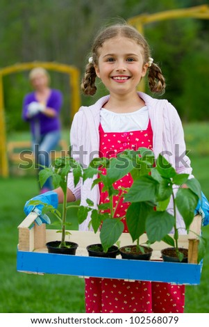 Gardening, planting concept - lovely girl working with mother in the garden
