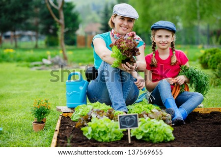 Gardening, planting - young girl with mother working in vegetable garden