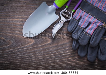 Gardening protective gloves hand spade and secateurs on vintage wooden board agriculture concept.