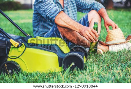 Gardening. Senior man take a rest in the yard and enjoying in beer after work with a lawn mower. Hobbies and leisure #1290918844